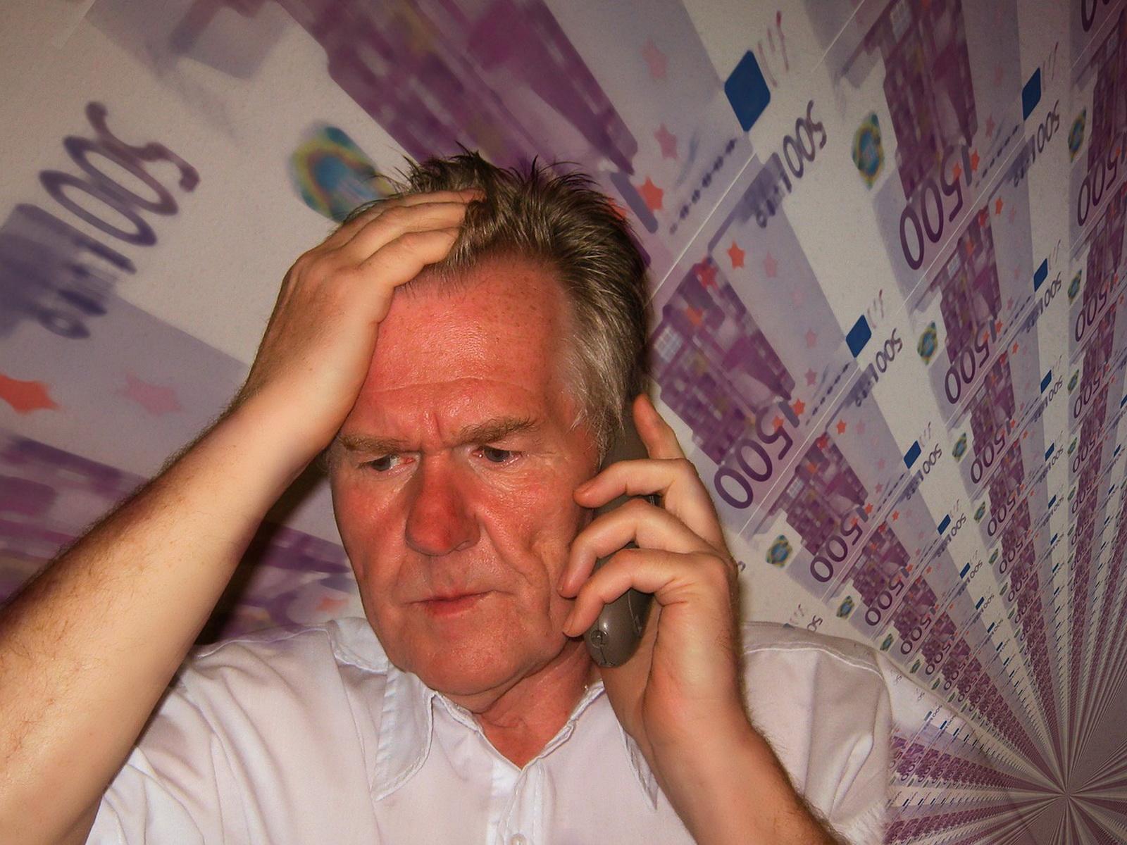 """Symbolfoto zum Thema """"Unseriöse Telefonwerber"""" - gestresster Mann am Telefon, im Hintergrund Geldscheine"""