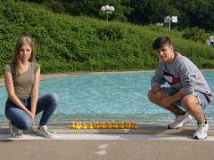 Zwei Praktikanten der ENRW verstecken 20 gelbe Enten im Freibad.