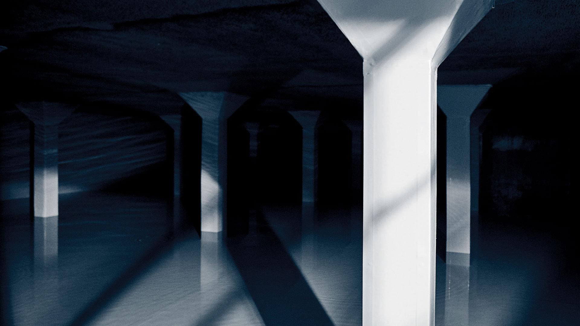 Hochbehälter von innen fotografiert. Das Bild ist sehr dunkel mit vielen Schatten und es ist Wasser im Hochbehälter enthalten