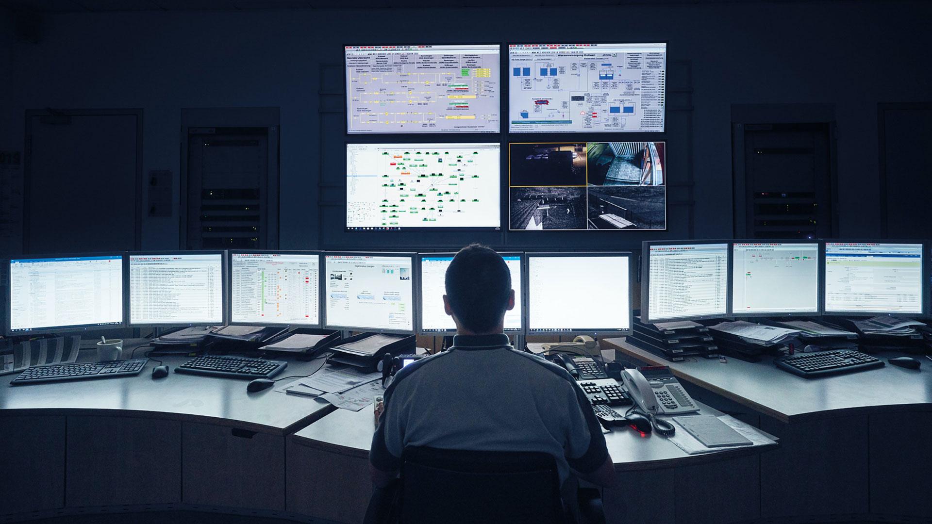 Mann sitz vor Bildschirmwand