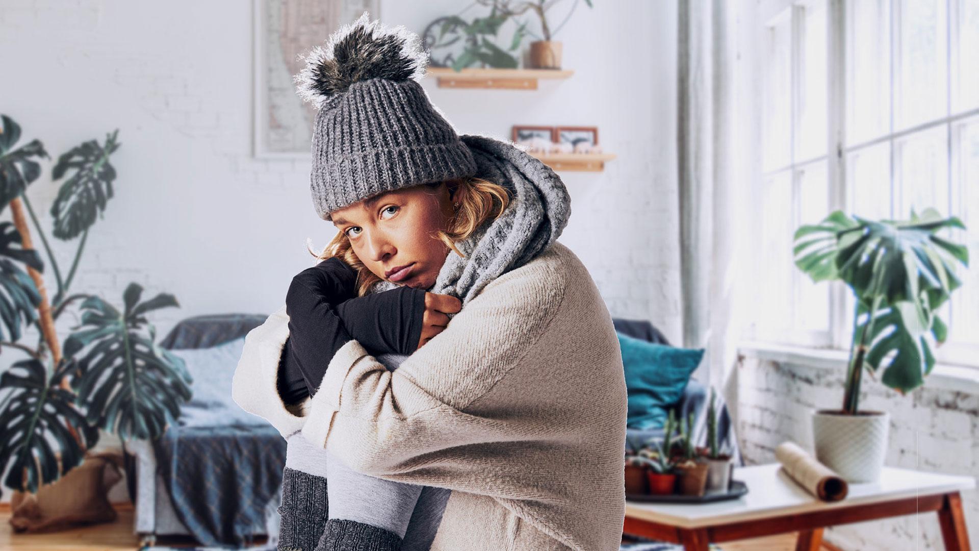 Frierende Frau sitzt im Wohnzimmer