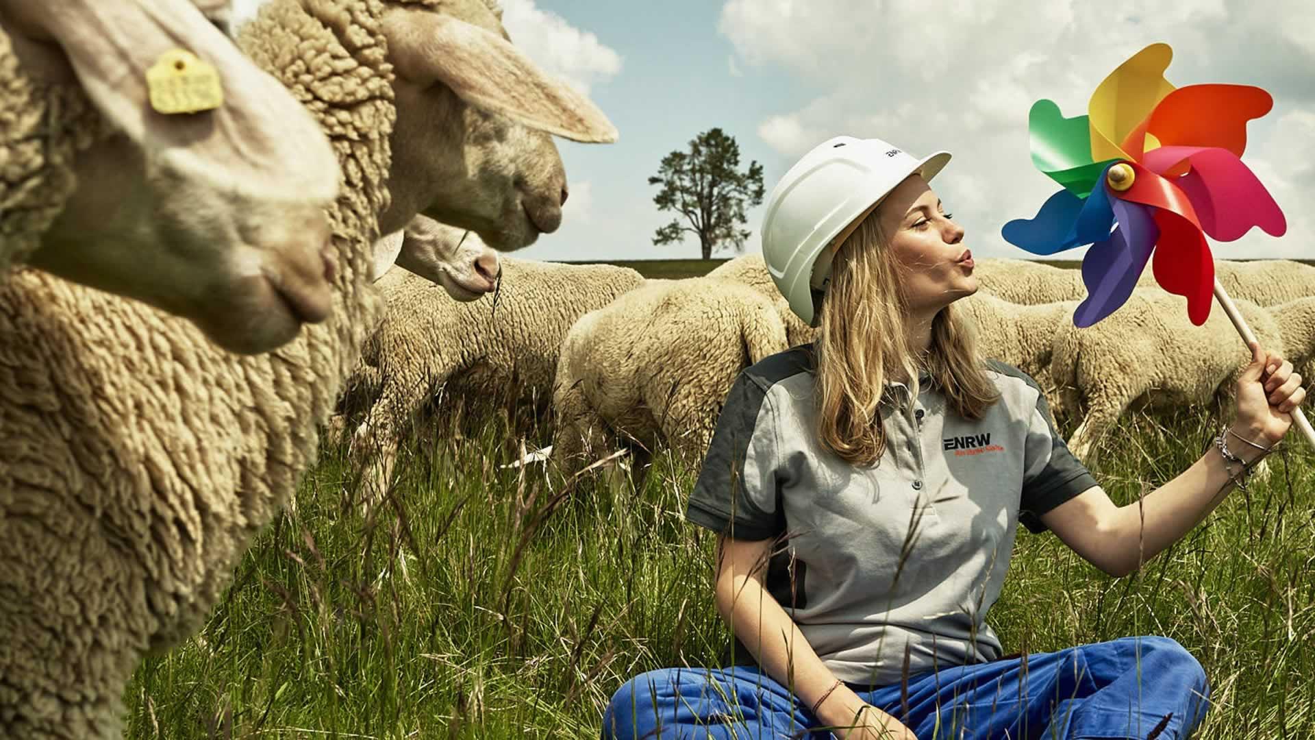 Frau sitzt aus einer Wiese mit Schafen im Hintergrund und pustet in ein buntes Windrad