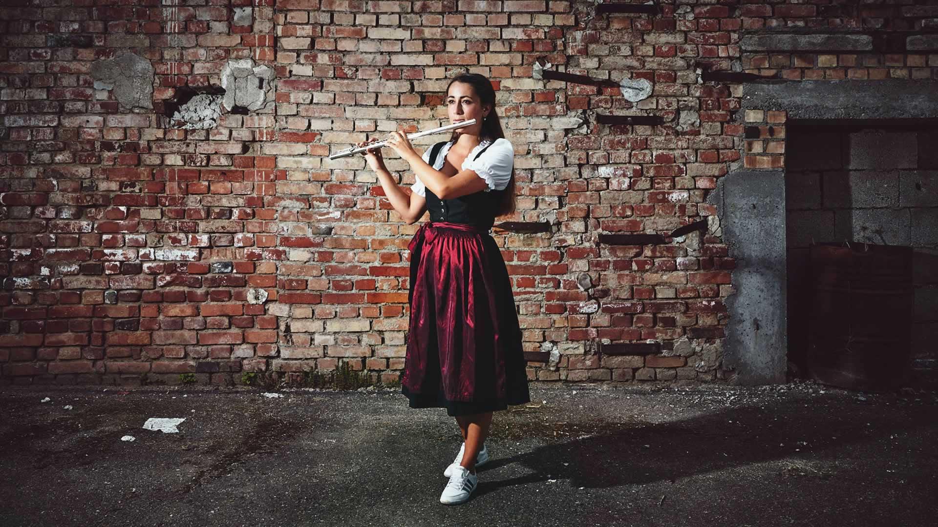 Frau in rot-schwarzem Dirndl spielt Querflöte vor einer Backsteinmauer
