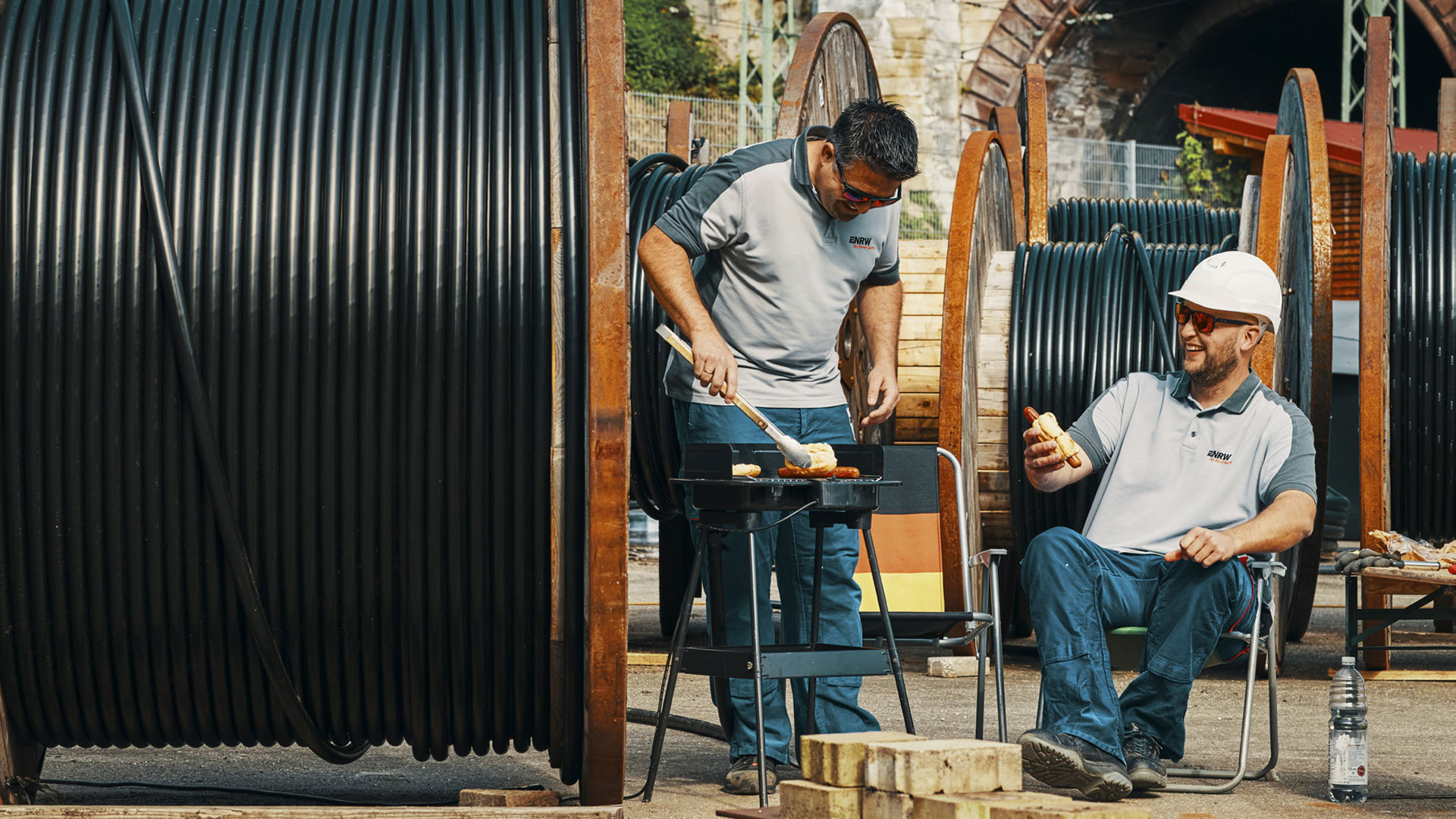 Zwei Männer grillen zwischen großen aufgerollten Leitungen