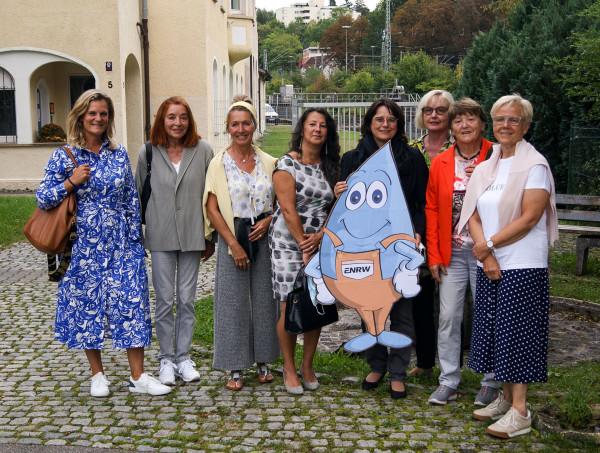 8 Frauen stehen mit Maskottchen Blubbi vor dem ENRW-Gebäude