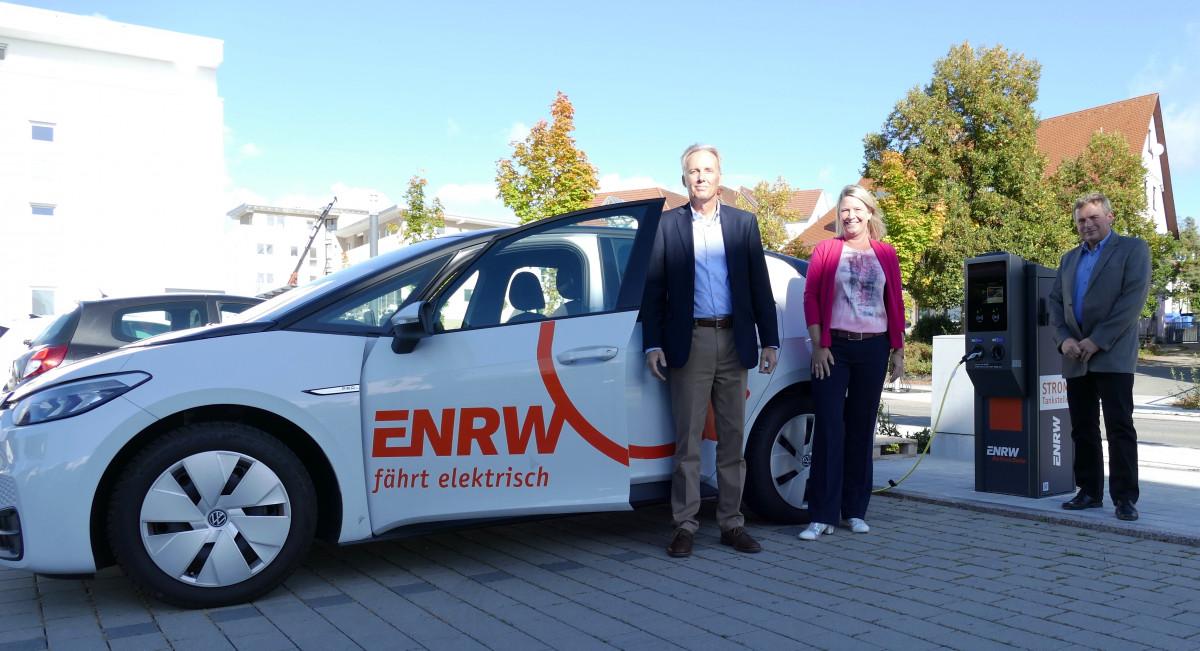 Zwei Männer und eine Frau stehen vor einem Elektroauto, das an einer Ladesäule aufgeladen wird.